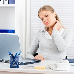 Businesswoman having pain in her neck
