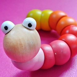 wooden colored caterpillar on pink background