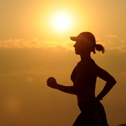 silhouette of lady running with hot sun in the background
