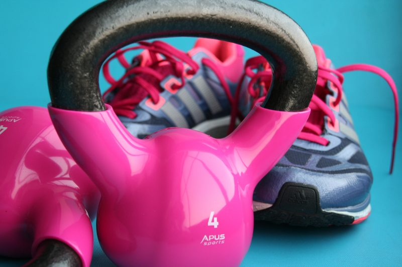 Pink Kettle bell with blue and pink sneakers behind it