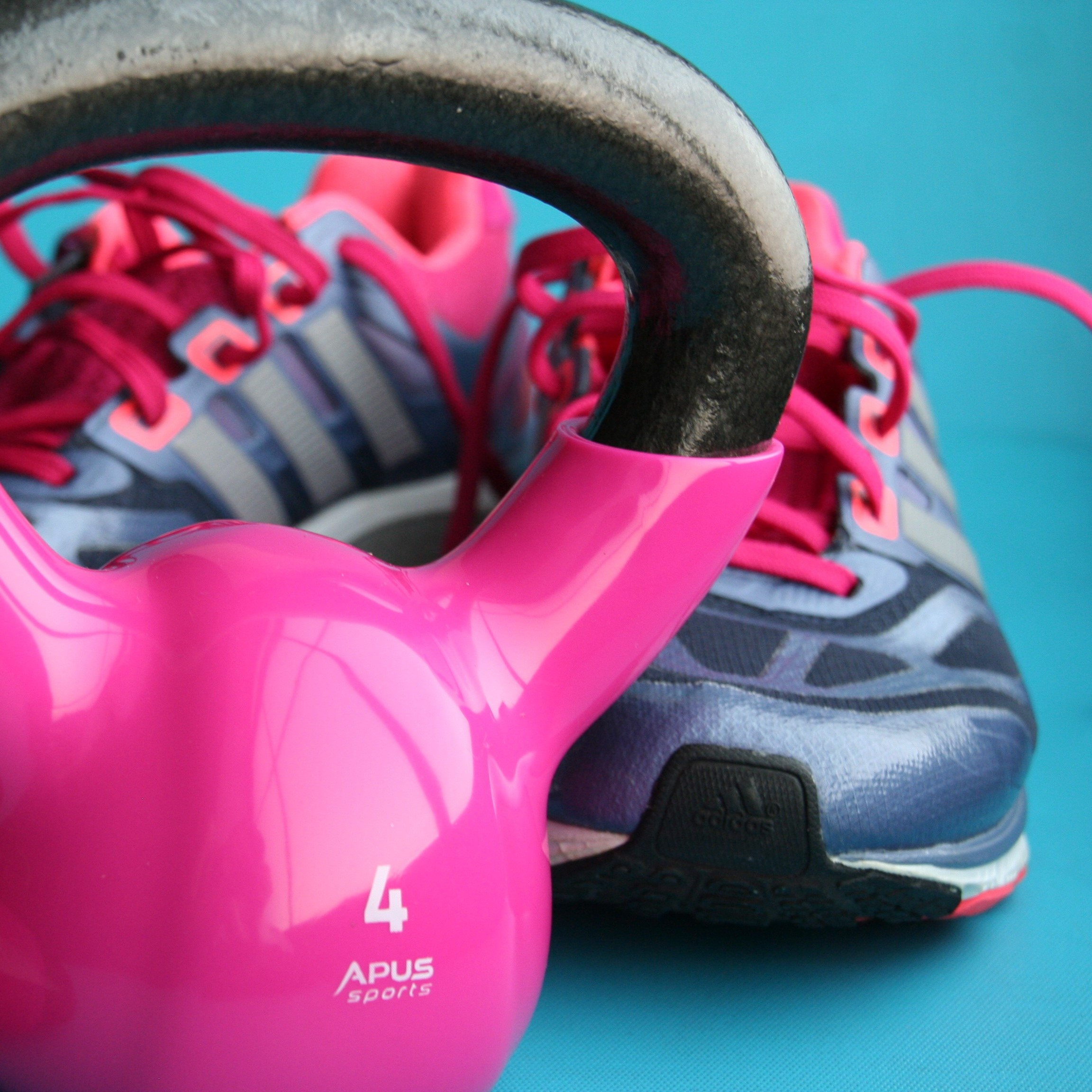 Pink kettle bell with a pair of blue and pink sneakers in the background